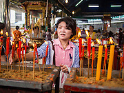 """26 AUGUST 2013 - BANGKOK, THAILAND: A woman lights candles and pray at the Poh Teck Tung Foundation for Hungry Ghost Month in Bangkok. Poh Teck Tung operates hospitals and schools and provides assistance to the poor in Thailand. The seventh lunar month (August - September in 2013) is when the Chinese community believes that hell's gate will open to allow spirits to roam freely in the human world for a month. Many households and temples will hold prayer ceremonies throughout the month-long Hungry Ghost Festival (Phor Thor) to appease the spirits. During the festival, believers will also worship the Tai Su Yeah (King of Hades) in the form of paper effigies which will be """"sent back"""" to hell after the effigies are burnt.      PHOTO BY JACK KURTZ"""