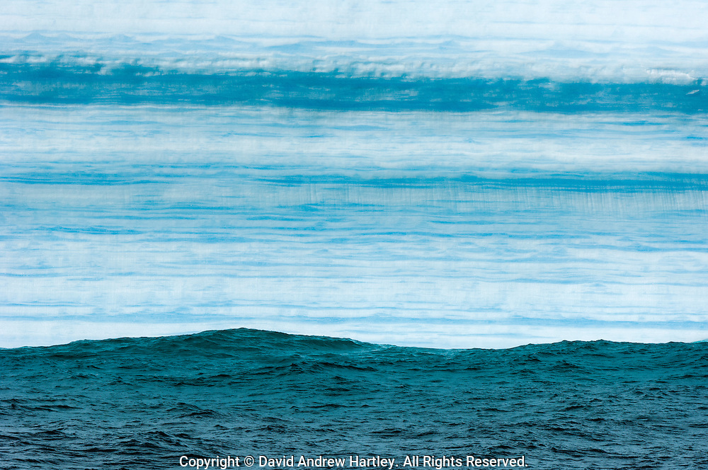 Waves roll past an iceberg featuring horizontal turquoise stripes, South Orkney Islands, Scotia Sea, South Atlantic Ocean