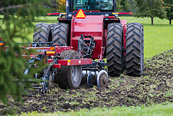 A farm implement referred to as a disc is pulled by a tractor to turn over sod