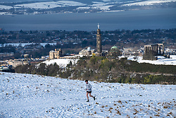 Edinburgh, Scotland, UK. 12 Feb 2021.  As the cold weather continues members of the public are out in Holyrood Park playing sport and making political slogans. Pic;  A lone runner on the snow covered Salisbury Crags with Calton Hill in the distance. Iain Masterton/Alamy Live news
