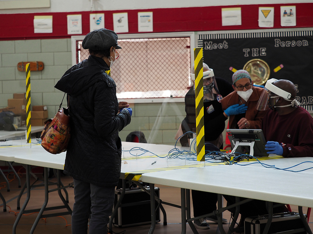 Poll workers wearing protective work behind a plastic shield as they check in a voter at a voting center in Baltimore. On April 28, 2020 a special election was held to fill the remainder of the term in the US House of Representatives for Maryland's 7th congressional district. Elijah Cummings, the incumbent representative, died in office on October 17, 2019.