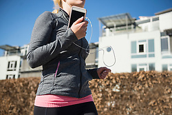 Woman jogging and listening music on smart phone