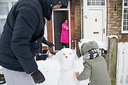 Young family in Kings Heath including a young girl seeing snow for the first time enjoy the heavy snow fall and build snow men on Sunday 10th December 2017 in Birmingham, United Kingdom. Deep snow arrived in much of the UK, closing roads and making driving treacherous, while many people simply enjoyed the weather.