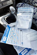 The completed test samples and instructions belonging to a middle-aged lady while sitting in the driver's seat of her car after a self-administered Coronavirus (COVID-19) test in south London. There are four steps to the self-administered Covid-19 test (inserting a swab into the nose and throat) which the public works through in their car, windows up and all communications with army personnel via phone, in a south London leisure centre, on 2nd June 2020, in London, England. The kit provided consists of a booklet, plastic bag, swab, vial, bar codes and a sealable biohazard bag. The swab sample is taken from the back of the throat and nasal passage with the contents sealed and returned to soldiers through a narrow window. The whole process takes between 5-10mins with results available with 48hrs.
