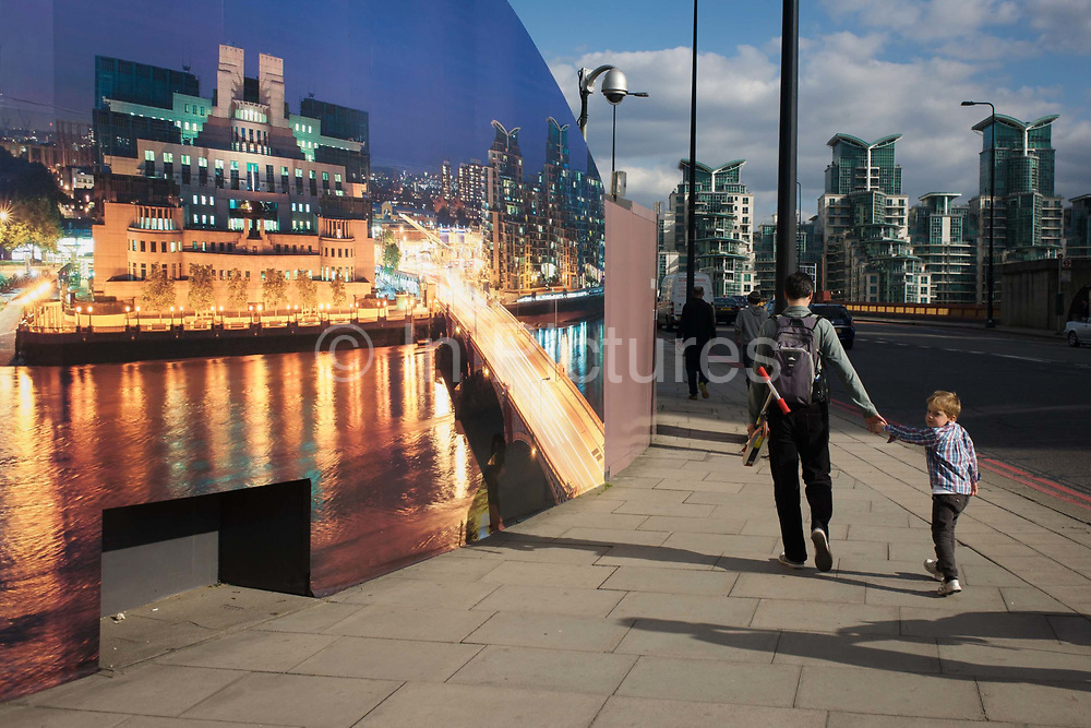 """A young boy looks over his shoulder by a construction hoarding, a night time panorama of the Thames south bank, featuring the HQ of the intelligence service (MI6) across the river in Vauxhall. Under the gaze of a CCTV camera, the lad glances back as his father leads him towards a local station. The temporary hoarding will stay in place for the time that the company's new residential riverfront apartments are under construction. In the image, the building at Vauxhall Cross, is located at 85 Albert Embankment beside Vauxhall Bridge. It is known within the intelligence community as """"Legoland"""" and """"Babylon-on-Thames""""."""