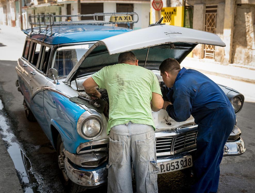 8 September 2015: Men repairing car on street in Havana, Cuba.