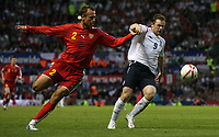 Photo: Paul Thomas.<br /> England v Macedonia. UEFA European Championships 2008 Qualifying. 07/10/2006.<br /> <br /> Wayne Rooney (R) of England get5s past Nikolce Noveski.