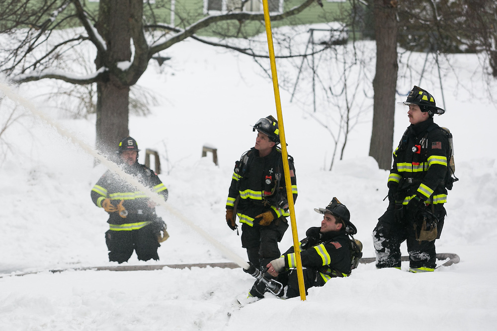 Hingham, MA 02/11/2013.Firefighters deploy a hose line in the snow at the scene of a 3 alarm house fire at 276 East St. in Hingham on Monday, February 11..Alex Jones / www.alexjonesphoto.com