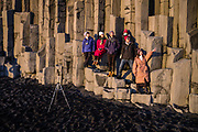 Vik i Myrdal, Iceland, 1 apr 2019, Sunset at Reynisfjara black sand beach. Asian tourist group making a team picture on the basalt rock formation