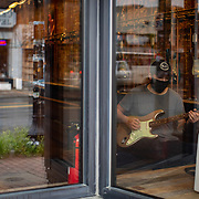 """CHARLOTTE NC - MAY 8:  Alex Thornton, a worker at Midwood Guitar Studio, can be seen through the front window as he plays guitar while he waits for customers in Charlotte, NC on May 8, 2020.  The studio has been closed since mid March, but they have been able to sell some things online. Commercial businesses that were deemed """"non-essential"""" are able to reopen at 5pm on May 8th under North Carolina Governor, Roy Cooper's phase 1 plan to reopen the state economy. (Logan Cyrus/ Bloomberg )"""