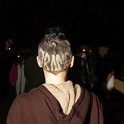"""A man with a haircut that reads """"Obama"""" celebrate in front of the White House in Washington DC after Barack Obama was announced the winner of the 2012 presidential elections."""