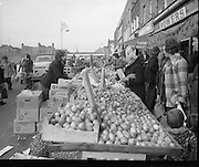 Moore Street, Dublin.      (J97)..1975..23.12.1975..12.23.1975..23rd December 1975..For well over a hundred years Moore Street has served the citizens of Dublin. The longest running open air fruit and vegatable market offers value for money,particularly to those where money is in short supply. Predominately a fruit and veg market there are several traders who sell fish and seasonal goods, as illustrated by the photographs showing turkeys and holly wreaths being sold on the run up to Christmas..Alongside the street traders,Moore Street was also a mecca for butcher shops. An Irish family could stock up on a weeks food requirements without leaving the street.