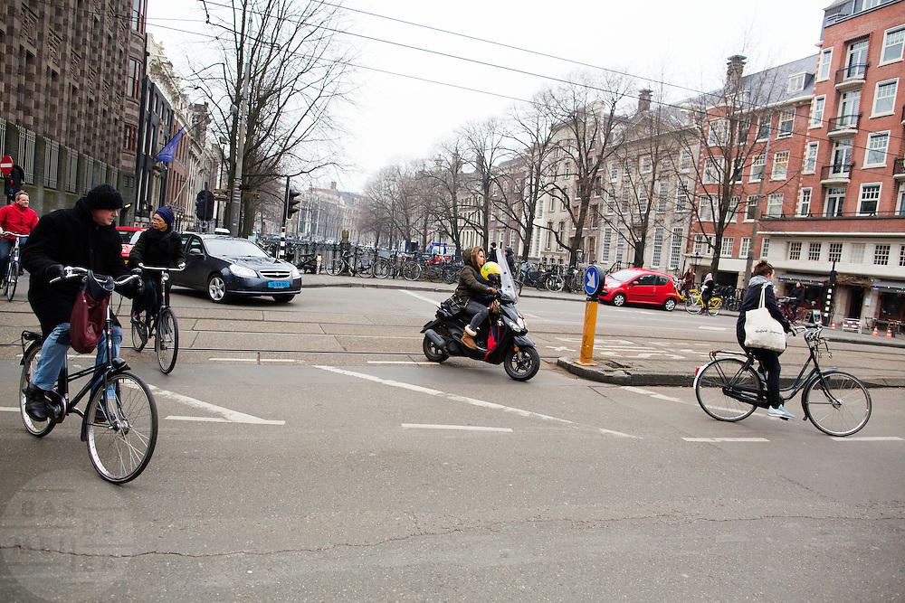In Amsterdam steken fietsers en een vrouw met kind op een scooter de Vijzelstraat over.<br /> <br /> In Amsterdam cyclists and a woman with a child on a scooter cross the Vijzelstraat.