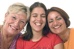 Three women; heads together; smiling,