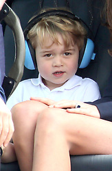 Prince George wears ear defenders as he sits in a helicopter with his mother the Duchess of Cambridge during a visit to the Royal International Air Tattoo at RAF Fairford - the world's largest military airshow.