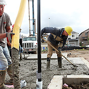 """Carl Kinonen pours concrete on the worksite while Kevin Hoffman of Habitat for Humanity smooths it. """"I love pouring concrete,"""" Hoffman said. """"At the end of the day, you can see what you've done.""""..John Gray was born 92 years ago and grew up poor in rural Oregon. He made a fortune in the chainsaw industry after World War II, and now he has donated more than a million dollars to Habitat for Humanity to buy land in Portland for low-income housing. Volunteers work to build solid foundations on the largest of these land parcels on Wednesday, May 2, 2012."""