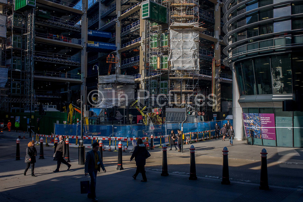 Pedestrians and large construction site on the corner of Wallbrook and Cannon Street in the City of London. As Londoners to and fro, we see the junction of streets in the heart of the capital's financial quarter - also known as the Square Mile - founded by the Romans in the 1st century. These streets still follow their medieval routes, with this section once a busy river Wallbrook tributary that passed downhill on its way to empty into the Thames. The construction project wiull be known as The Wallbrook Building in its own Wallbrook triangle. Minerva are the developers, coincidentally, the Roman Godess of  goddess of wisdom and sponsor of arts, trade, and strategy.