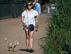 © Licensed to London News Pictures. 13/06/2021. London, UK. A woman walks her dog in the early morning warm weather in Hyde Park central London on a hot summer's day. Temperatures in the capital are expected to reach a high for the year. Photo credit: Ben Cawthra/LNP