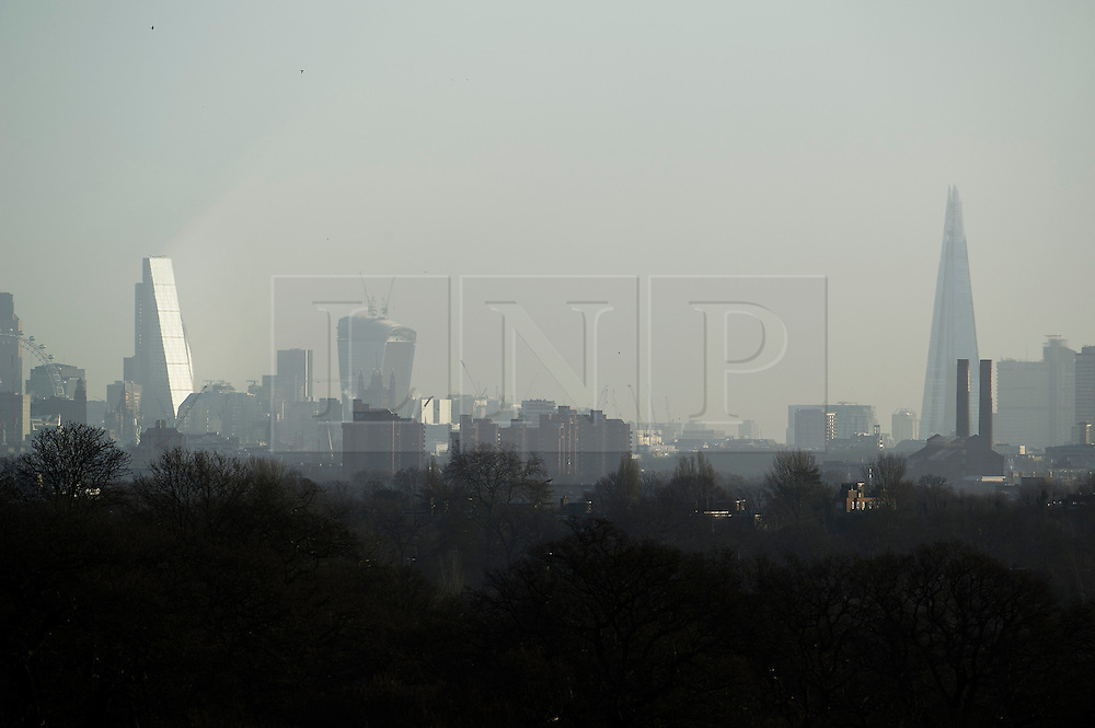 © London News Pictures. 22/02/2014. London, UK.  Light reflecting off the Leadenhall Building (left) nicknamed The Cheesegrater with The Shard (right) and 20 Fenchurch Street (centre) also known as the Walkie Talkie Building', at sunrise, seen from Richmond Park in West London. The south of England is experiencing warm weather for the time of year and sunshine following weeks of rain and flooding.  Photo credit: Ben Cawthra/LNP