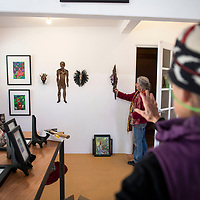 Candace Lee holds a piece of art against the wall as Be Sargent prepares to hang it at OPO on Second St. in Gallup Wednesday, Oct. 10, 2018 for arts crawl this weekend.