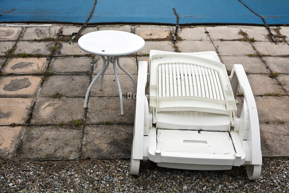 folded plastic reclining chair with table by a closed up swimming pool