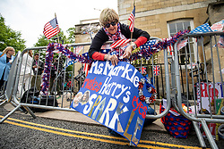 © Licensed to London News Pictures. 16/05/2018. Windsor, UK. Donna Werner, who has travelled from Connecticut in the USA for the Royal Wedding, attaches one of the banners she made with her daughter to fencing opposite Windsor Castle. Prince Harry and Meghan Markle are to be married on Saturday in Windsor. Photo credit: Rob Pinney/LNP