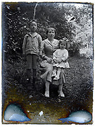 mother posing with children in outdoors setting deteriorating glass plate 1900s