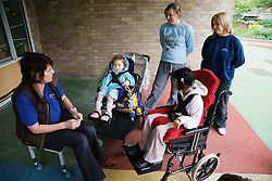 Carers talking to children outside classroom,