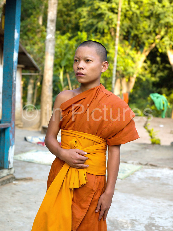 Portrait of a young novice Buddhist monk wearing an orange robe before a ceremony at the 480 year old temple in Ban Mouanghoun, Phongsaly province, Lao PDR. Although there are several villages with temples along the Nam Ou river, the remote and roadless Ban Mouanghoun is the only village in this area with its own resident monks who are also required to perform ceremonies at all the local villages. Lao Buddhists are very devout and almost every Lao man joins a monastery, or temple, for at least a short period of time. Many men also become monks for the rest of their lives. Ban Mouanghoun will be relocated due to the construction of the Nam Ou Cascade Hydropower project Dam 5.