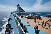 Passengers are seen on the deck of the Grimaldi Lines Cruise Barcelona during the Barcelona-Civitavecchia trip, in Italy, on Tue., June 11, 2013.  Photographer: Víctor Sokolowicz/Bloomberg.