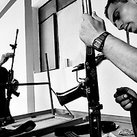 Police officers clean their weapons between patrols.  Saravena is one of the most dangerous places in Colombia. The police station was attacked with homemade mortars 85 times in one year. Assassinations, sniper attacks and bombs are almost daily occurrences.<br />