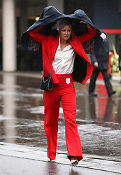 A racegoer shields herself from the rain during Gold Cup Day of the 2019 Cheltenham Festival at Cheltenham Racecourse.