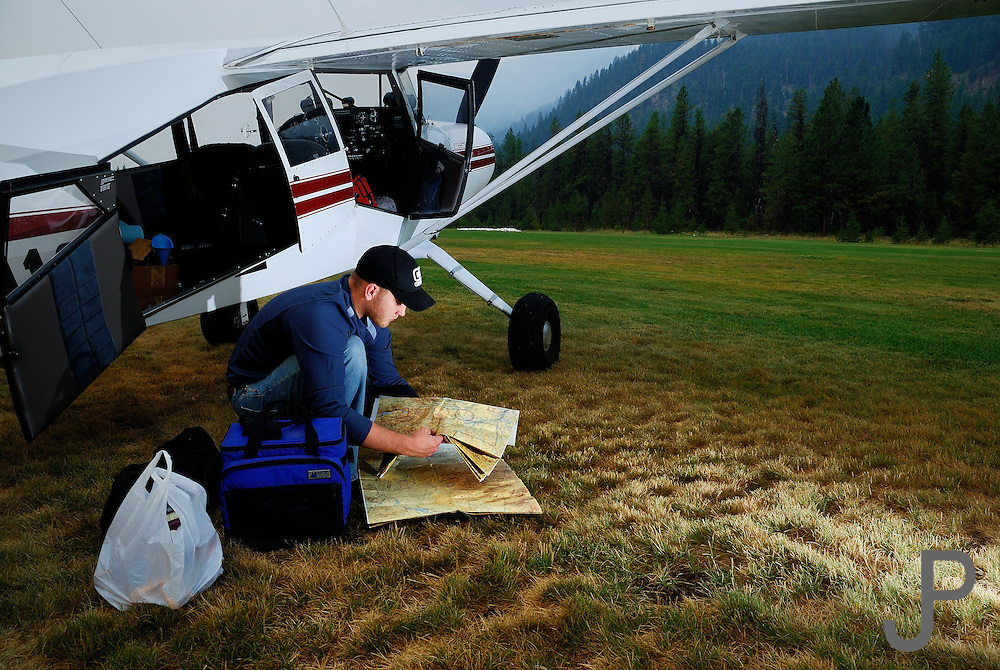 Adam Pratt checking charts before flying Maule M7-235C at Johnson Creek, ID