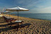 Beach chairs and umbrellas in early morning light, with Bali's sacred mountain, Gunung Agung, in background. Sanur Beach, Bali, Indonesia.