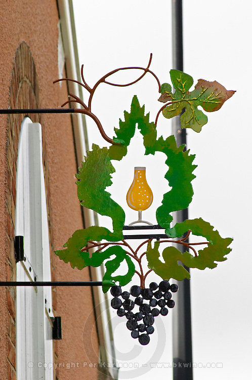 A wrought iron painted sign that illustrates the theme of champagne and wine production: a stylised leaf and vine with a glass of wine and a bunch of grapes, the village of Hautvillers in Vallee de la Marne, Champagne, Marne, Ardennes, France