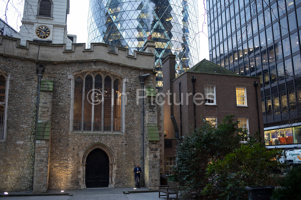 Man dwarfed by the scale of buildings texting while standing outside St Helens Church, Bishopsgate in the City of London on 5th February 2020 in London, England, United Kingdom. The City of London is a city, county and a local government district that contains the historic centre and the primary central business district CBD of London.