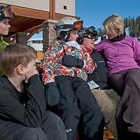 A family relaxes on the sun deck at Big Sky ski area, Big Sky, Montana.