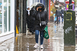 © Licensed to London News Pictures. 10/05/2021. London, UK. A woman is caught in heavy rainfall in north London. More rain is forecast for the South East of England this week. Photo credit: Dinendra Haria/LNP
