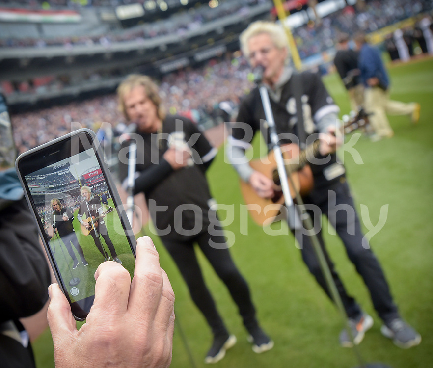 Members of the REO Speed Wagon Dave Amato and Kevin Cronin are recorded with a cell phone while they sing the National Anthem before the start of the Chicago White Sox 2017 home opener at Guaranteed Rate Field in Chicago.