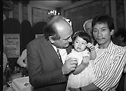 Vietnamese Refugees are Naturalised.  (R61)..1987..08.07.1987..07.08.1987..8th July 1987..A large group of Vietnamese refugees were presented with certificates of naturalisation by Justice Minister, Gerard CollinsTD at the dept of Foreign Affairs in Iveagh House today. The vietnamese were dispossed due to the Vietnam war.The group ,consisting of 156 adults, arrived in Ireland from Vietnam and some refugee camps inHong Kong and Malaysia...Image shows Trieu Trien Minh and daughter Christina (2) with Minister Gerard Collins at the reception after the presentation of the naturalisation certificates.