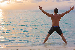man stretching  while standing in the ocean while the sun sets in Bermuda