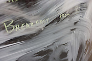 A cafe offering breakfasts for £1.95 Pounds in central London has closed, a victim of the UK recession. Swirls of emulsion paint on the business's window creating abstract patterns on the glass. Around a recession-bled Britain, high-street businesses have been going bust in their thousands. Britain has now endured eight recessions since the Second World War. No two recessions are alike, and that applies to the current slowdown also. It has been caused by a shock to the availability of credit, a massive build up of debt. The number of people out of work currently stands at almost two million. Given the rate at which the economy is deteriorating this could easily be above three million. From a continuing piece of work about windows and urban messages, the picture is from the project of closed business windows: 'Bust - the Art of Recession'.