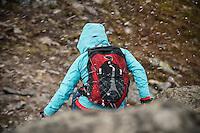 Female hiker is summer snow flurry near summit of Festvågtind, Austvågøy, Lofoten Islands, Norway