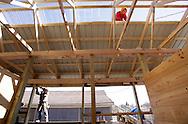 Joe Crawford of Chessari Construction from Pine Bush works on the roof of a new barn under construction at Historic Track in Goshen on Thursday, March 3, 2011. Santos Avila of Chessari Construction is at left. The 18-stall barn is scheduled to be completed in the next few months and will bring the total number of stalls at the track to 123.