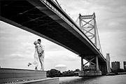 A bride and groom at Race Street Pier underneath the Benjamin Franklin Bridge in Philadelphia, Pennsylvania.