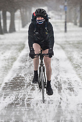 © Licensed to London News Pictures. 01/03/2018. London, UK. A cyclist makes his way to work on Clapham Common wearing shorts after more snow fell overnight. The 'Beast from the East' and Storm Emma have brought extreme cold and heavy snow to the UK. Photo credit: Peter Macdiarmid/LNP