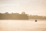Landscape with two people in a rowboat in the San Juan River at sunrise and silhouetted trees, El Castillo, Rio San Juan Department, Nicaragua