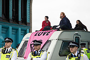 Environmental activists from Extinction Rebellion sit on top of a caravan used to block Tower Bridge during an Impossible Tea Party event on 30th August 2021 in London, United Kingdom. Extinction Rebellion were drawing attention to financial institutions funding fossil fuel projects whilst calling on the UK government to cease all new fossil fuel investment with immediate effect on the eighth day of their Impossible Rebellion protests in London.