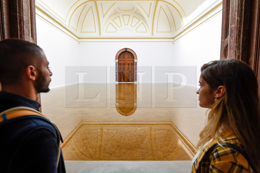 """© Licensed to London News Pictures. 17/09/2019. LONDON, UK. Visitors view """"Host"""", 2019, by Antony Gormley, made from Buckinghamshire clay and Atlantic seawater. Preview of a new exhibition by Antony Gormley at the Royal Academy of Arts.  The show bring together existing and specially conceived new works from drawing to sculptures to experimental environments to be displayed in all 13 rooms of the RA's Main Galleries 21 September to 3 December 2019.  Photo credit: Stephen Chung/LNP"""