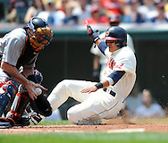 Shin-Soo Choo, from Korea, of the Cleveland Indians scores a run as Minnesota catcher Mike Redmond takes a relay throw..TThe Minnesota Twins defeated the Cleveland Indians 4-2 on Sunday, July 27, 2008 at Progressive Field in Cleveland.